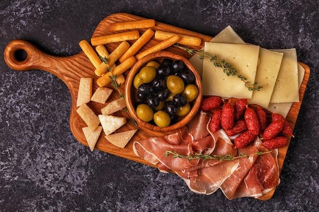 Sausage olives prosciutto cheese bread sticks wine