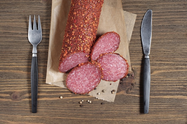 Sausage salami slices and cutlery on old wooden table, top view