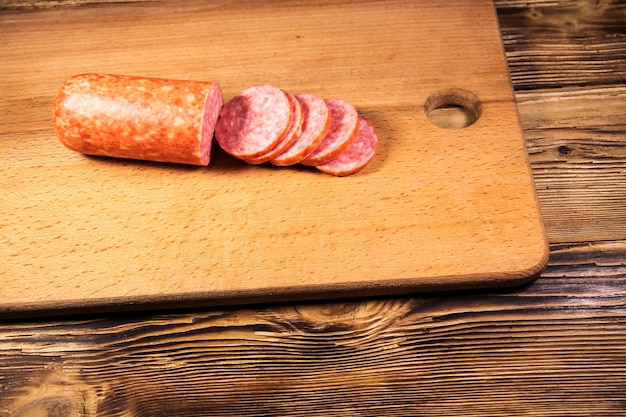 Sausage sliced on cutting board on wooden table
