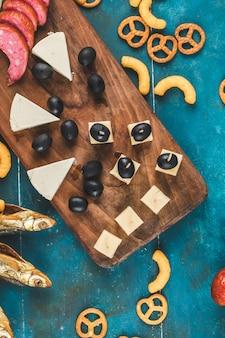 Fette di salsiccia con cubetti di formaggio, olive e cracker con pesce secco sul tavolo blu, vista dall'alto
