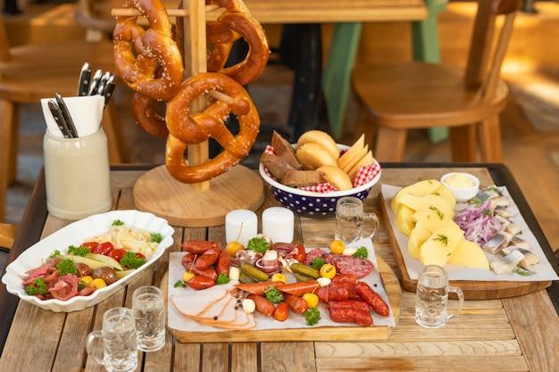 Колбаса с сыром и ферментированными огурцами, крендели закуски с водкой на столе