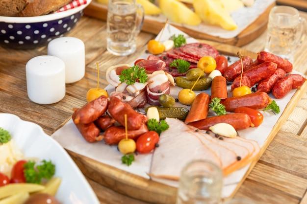 Колбаса с сыром и ферментированными огурцами, закуски с водкой на столе