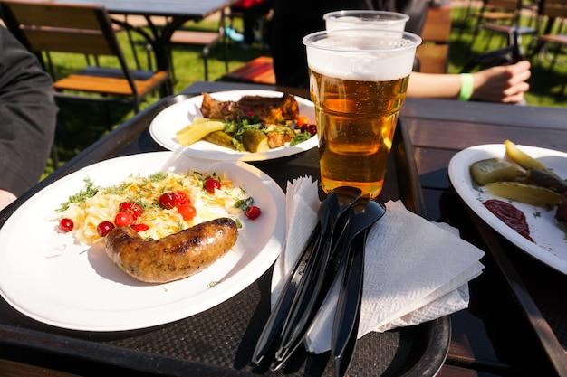 Колбаса с салатом на тарелке и светлым пивом на подносе уличной еды