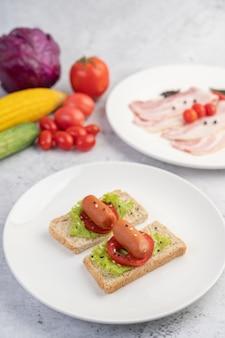 トマト、サラダ、白い皿に2セットのパンとソーセージ。