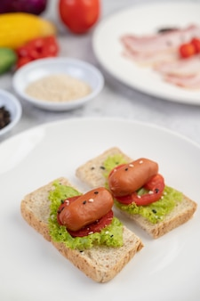 Sausage with tomatoes, salad and two sets of bread on a white plate.