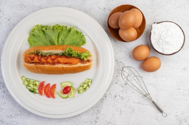 Salsiccia avvolta nel pane e lattuga condita con salsa.