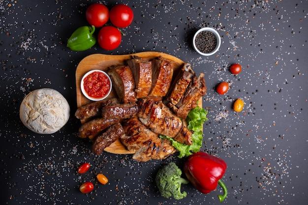 Сосиски и запеченное мясо с красным соусом, на черном с помидорами, красным зеленым перцем и брокколи, хлеб