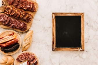 Sausages and buns near chalkboard