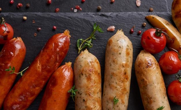 소시지와 요리 재료. 허브와 향신료를 더한 구운 소시지