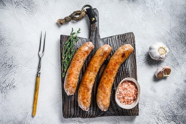 Сосиски барбекю, обжаренные со специями и зеленью на деревянной разделочной доске