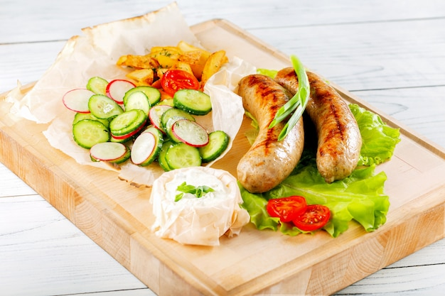 Sausages fried with sause and vegetables on wooden plate.