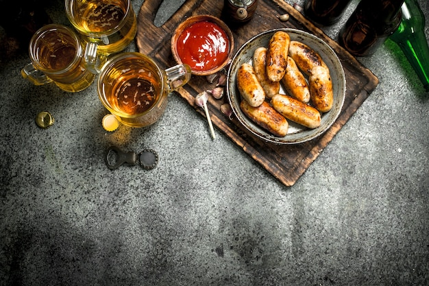Sausages in a frying pan with a cold beer on rustic table.