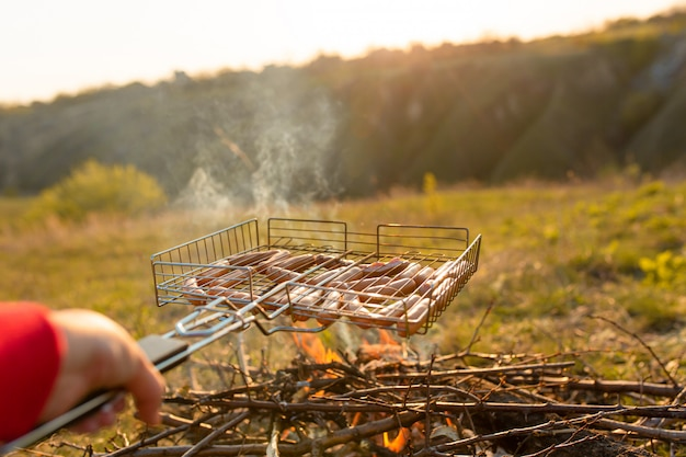 Sausages in the grill at the stake. a picnic in nature at sunset. taste of summer
