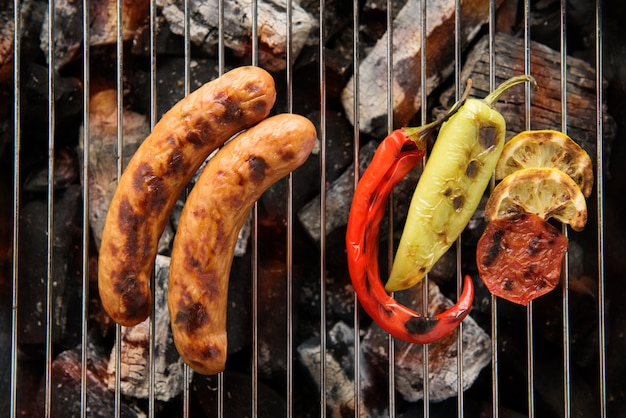 Sausages and grilled vegetables on the grill close up