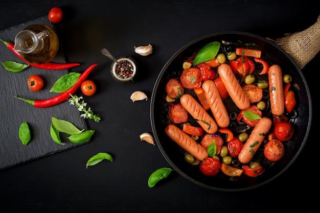 Колбаски гриль с овощами в греческом стиле на сковороде.