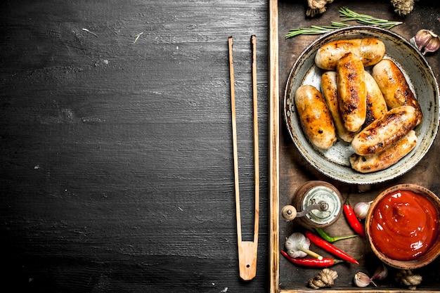 Сосиски на сковороде с соусом на деревянном подносе на черной доске