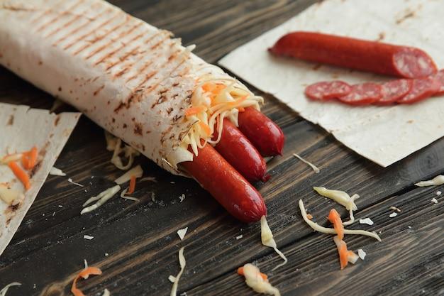 Колбаски в лаваше на деревянных фоне