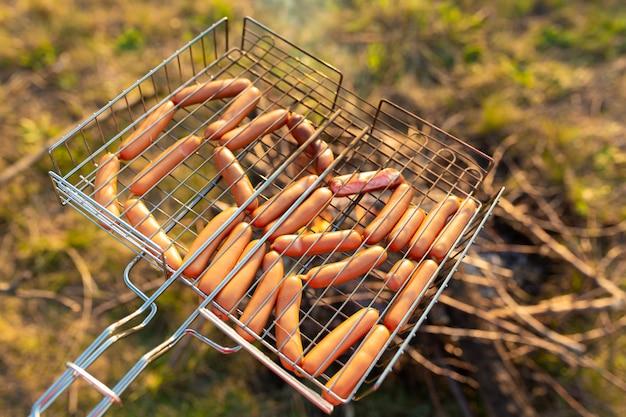 Колбаски в гриле на костре. пикник в природе на закате. вкус лета.