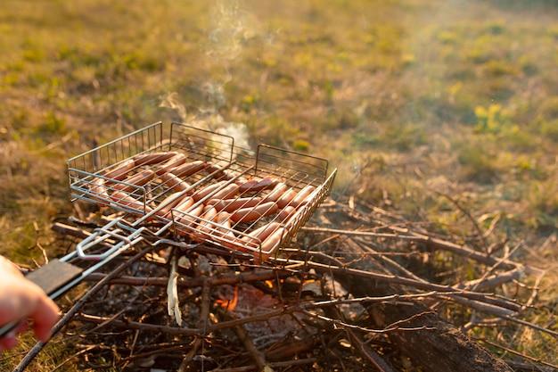 危機にsaしたグリルのソーセージ。日没時の自然の中でのピクニック。夏の味。