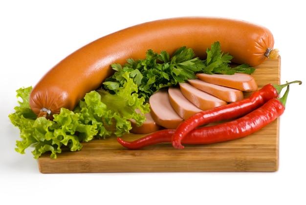 Сосиски на деревянной тарелке с салатом, петрушкой и перцем