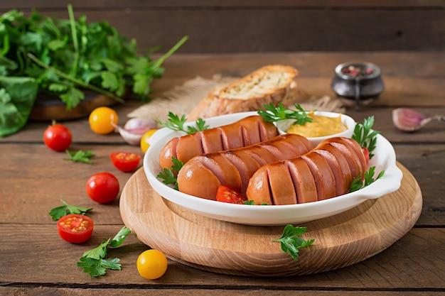 Колбаски на гриле сковороду на деревянном столе