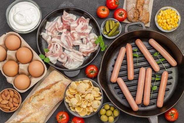 Sausages in pan. bacon cheese, vegetables, cookies cereal yogurt: ingredients for  continental breakfast