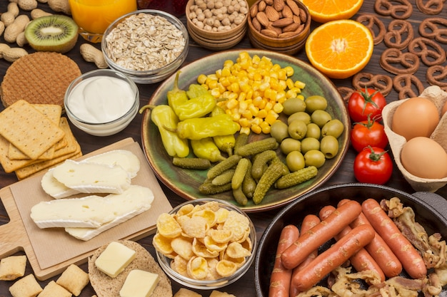 Sausages in pan. cheese, vegetables, cookies cereal: ingredients for  continental breakfast. balanced diet food. flat lay. copy space.