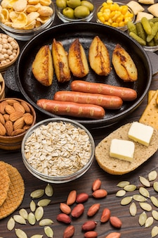 Sausages in pan. cheese, vegetables, cookies cereal: ingredients for  continental breakfast.
