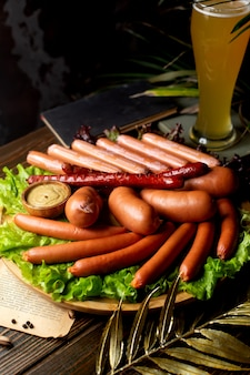 Колбаски подаются с горчицей и бокалом пива