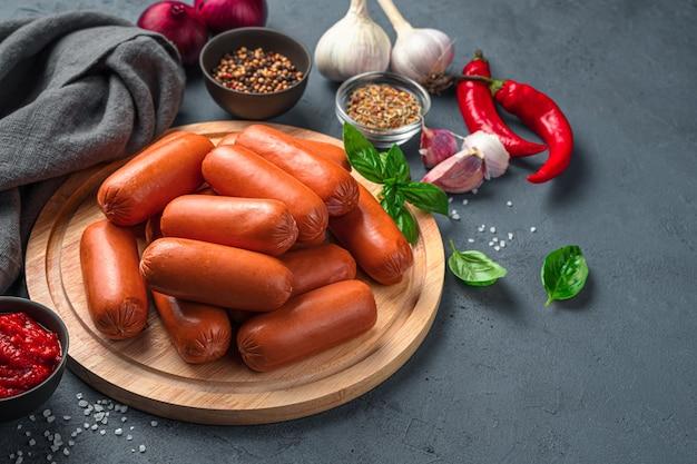 어두운 배경에 소시지, 토마토, 후추, 향신료. 측면 보기, 복사 공간