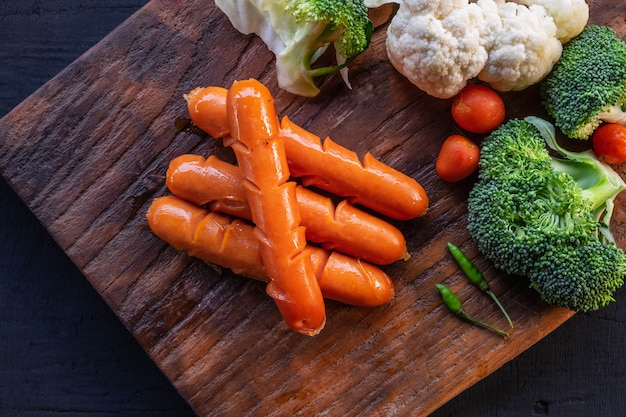 Sausages and vegetables on a wooden cutting board