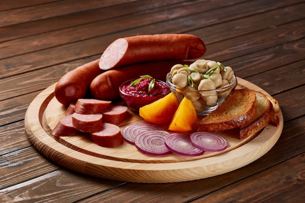 Колбаски с гарниром из овощей и зелени с соусами и хлебом на деревянной тарелке на темном деревянном столе.