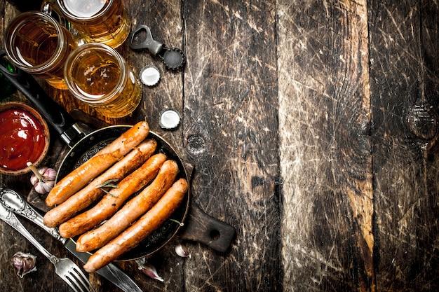 Колбаски с холодным пивом и соусом на деревянном фоне