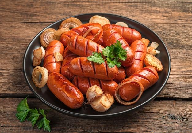 나무 배경에 튀긴 양파, 마늘, 신선한 파슬리를 넣은 소시지. 확대.