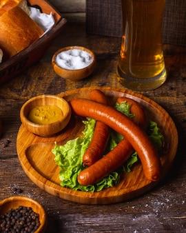 Колбаски с горчицей, солью, перцем и бокалом пива
