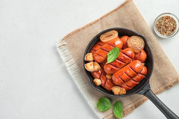 향신료와 바질을 곁들인 회색 배경에 양파와 마늘을 넣은 소시지