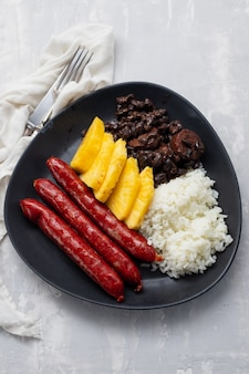 ダークディッシュにご飯、黒豆、パイナップルを添えたソーセージ