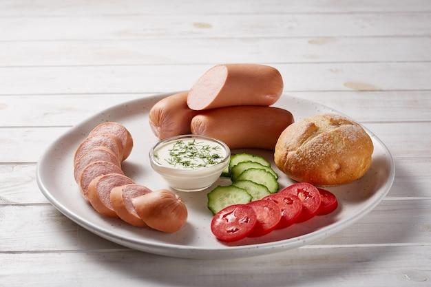 Сосиски с овощами и зеленью украшают соусами и хлебом на серой керамической тарелке на белом деревянном столе.