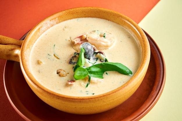 Обжарить морепродукты в сливочном соусе. тушеные креветки, мидии, осьминоги и кальмары в глиняной миске на яркой поверхности