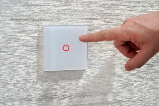 エネルギー節約の概念、電気スイッチに触れる指のクローズアップ。男の指が白い壁にあるタッチセンサー式のモダンなスイッチを押します。