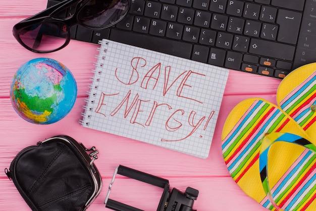 ピンクのテーブルトップの背景に女性の旅行者アクセサリーメガネ財布とビーチサンダルでノートブックのエネルギーを節約します。グローブと黒のキーボード。