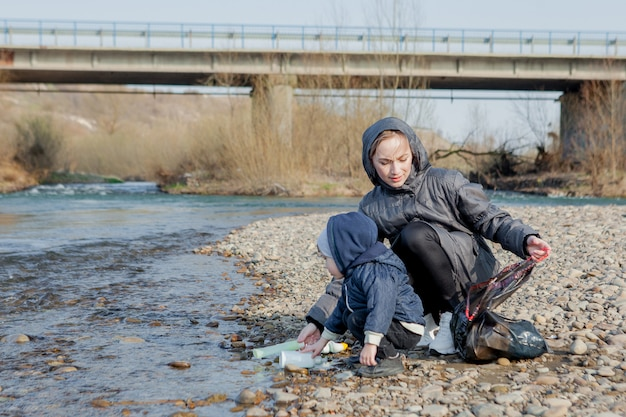 環境コンセプトを保存して、小さな男の子と彼の母親はビーチでゴミやペットボトルを収集してゴミ箱に捨てています。