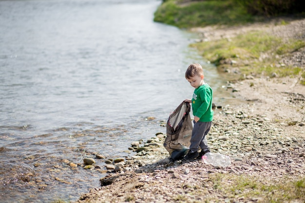 環境コンセプト、小さな男の子がビーチでゴミやペットボトルを収集してゴミ箱に捨てるのを保存します。