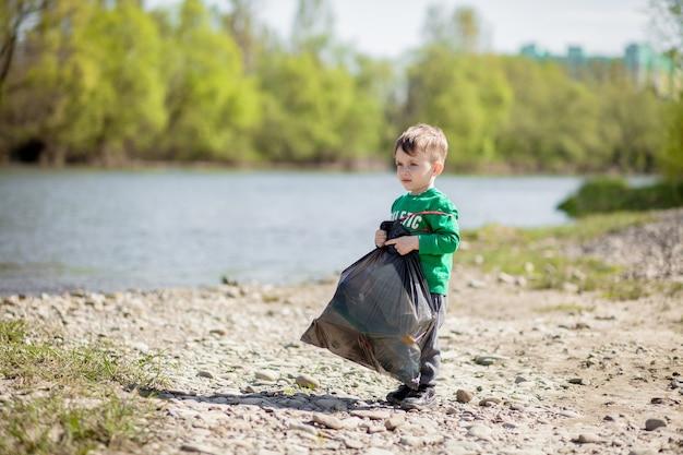 環境の概念を保存します。小さな男の子がビーチでゴミやペットボトルを集めてゴミ箱に捨てます。