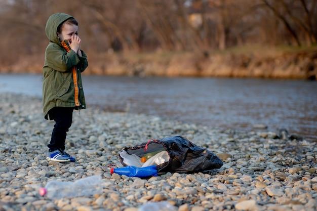環境コンセプト、小さな男の子が川でゴミやペットボトルを集めてゴミ箱に捨てる