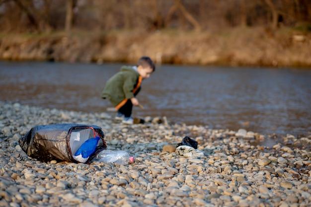 環境の概念を保存、小さな男の子がビーチでゴミやペットボトルを収集してゴミ箱に捨てる