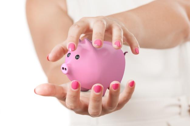 투자 개념을 저장합니다. 흰색 바탕에 핑크 돼지 저금통을 보호 하는 두 여자 손.
