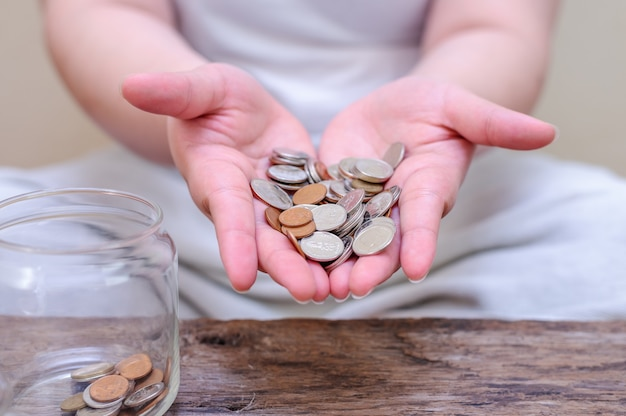 Save money and account banking for finance concept. hand with coin on blurred background