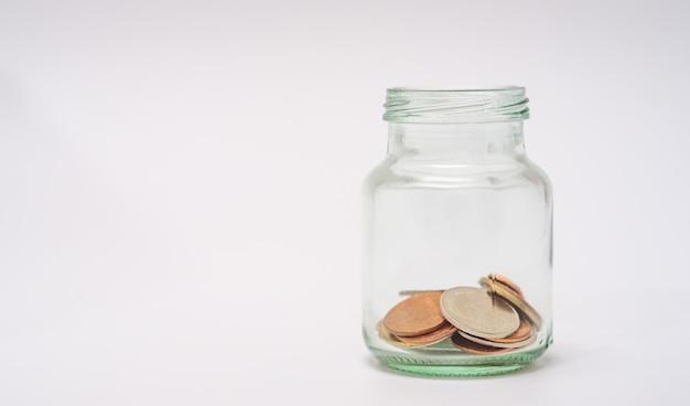 お金を節約し、金融の概念、白い背景の上のボトルのコインのアカウントバンキング