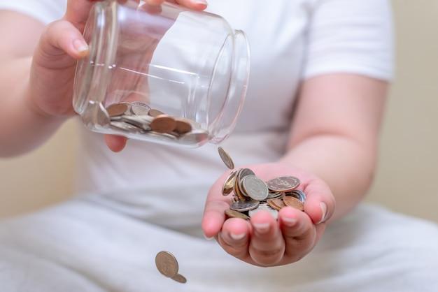 Сэкономьте деньги и банковский счет для концепции финансов, рука с размытой поверхностью бутылки с монетами